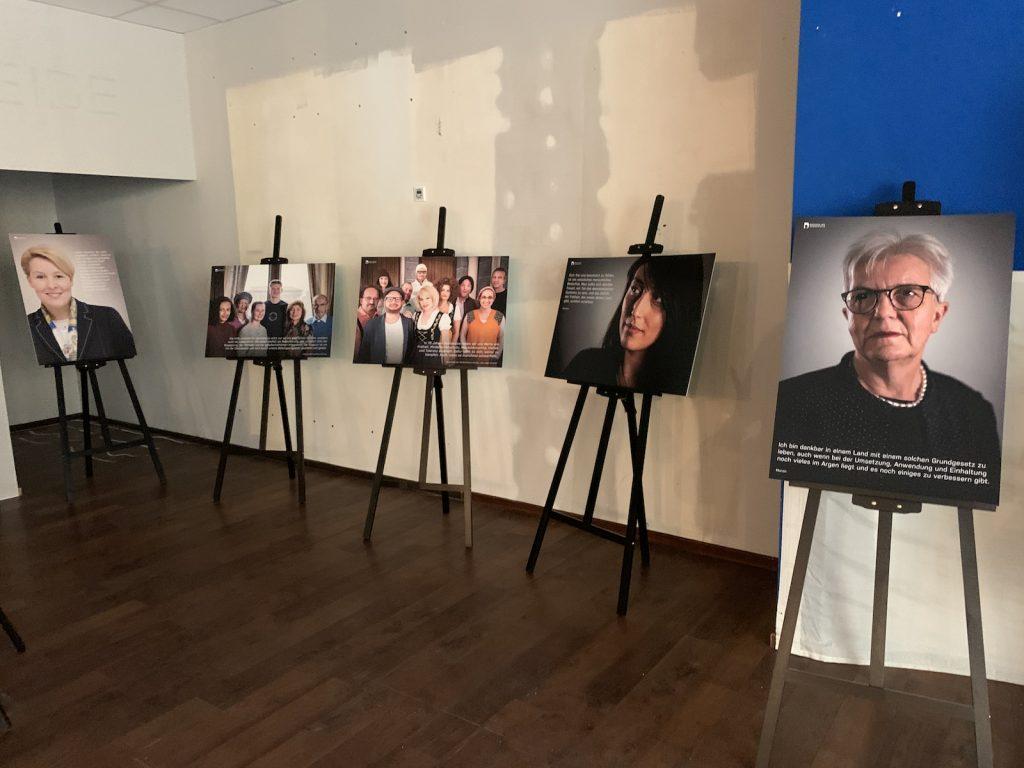 Kunst-Ausstellung Gesichter der Demokratie: Menschen sind einzeln oder in Gruppen auf Leinwänden abgebildet. Ein Zitat der Menschen zum Thema Demokratie steht daneben.